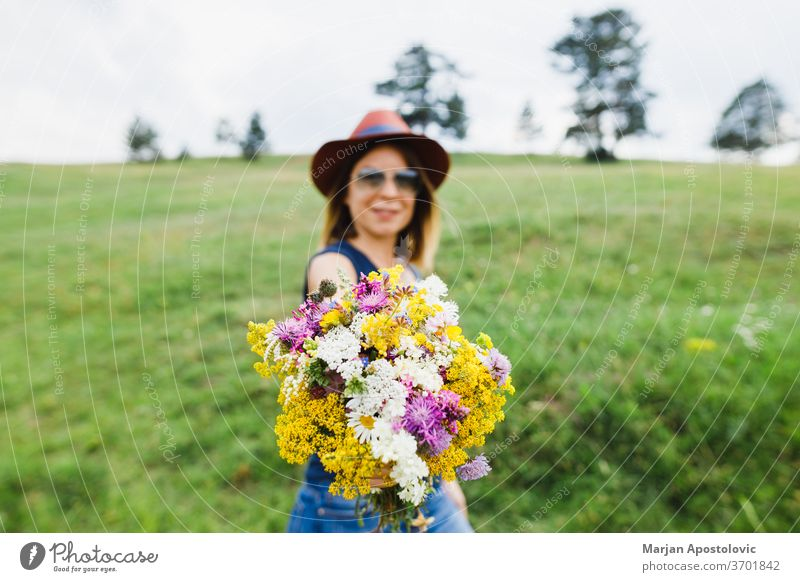 Junge Frau hält Blumenstrauss auf dem Feld Erwachsener schön Schönheit Blumenstrauß Haufen sorgenfrei lässig Charme farbenfroh Land niedlich Umwelt modisch