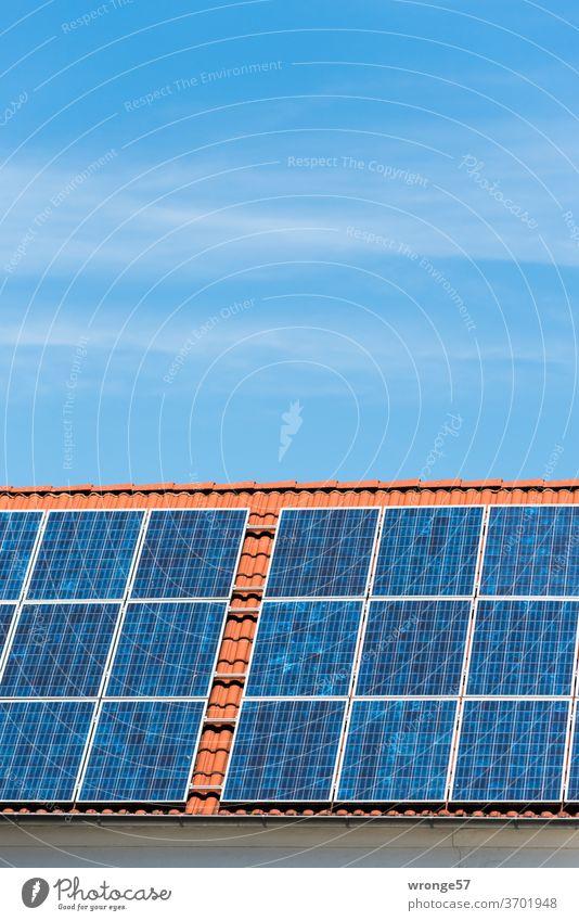 Nahaufnahme einer Solaranlage auf einem roten Ziegeldach unter blauem Himmel Sonnenenergie Solarenergie Photovoltaikanlagen Solarzellen Elektrizität Farbfoto