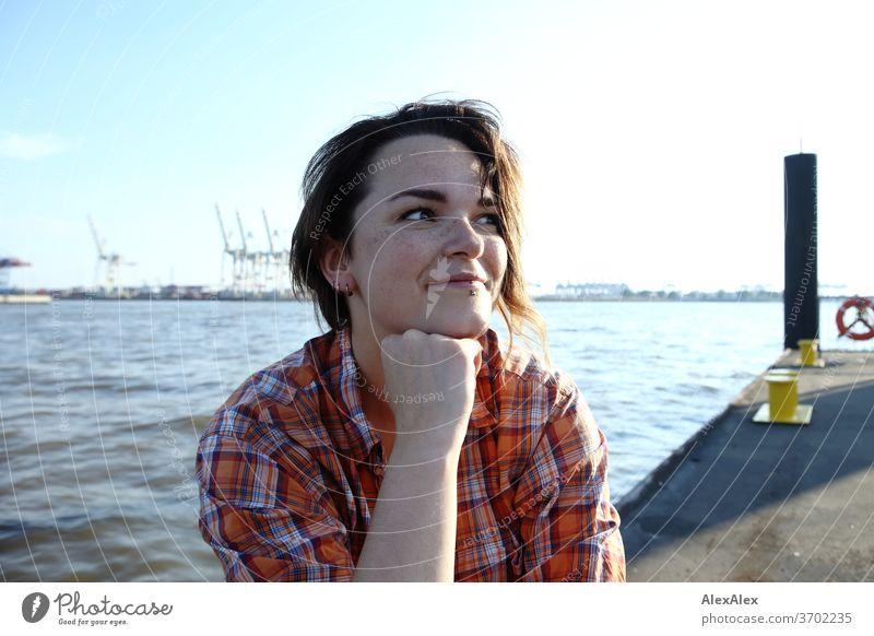 Junge Frau mit Sommersprossen sitzt auf einem Ponton vor Hamburger Hafen Porträt Zentralperspektive Blick brünettes Haar Textfreiraum rechts sommersprossig