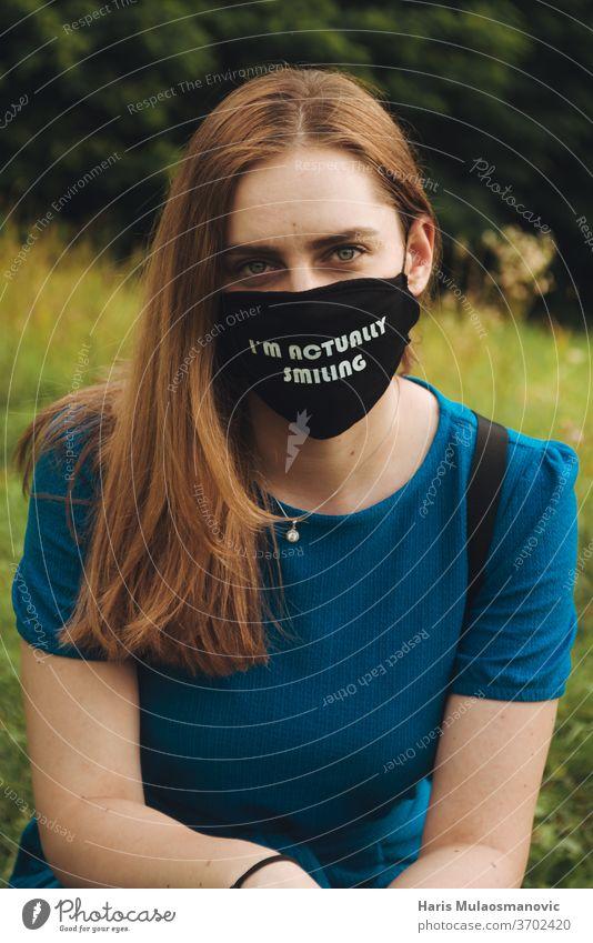 Frau mit Maske im Freien mit Text Ich lächle tatsächlich lässig Konzept Korona-Maske Corona-Virus Coronavirus covid-19 Kultur Bildung täglich Gesundheit