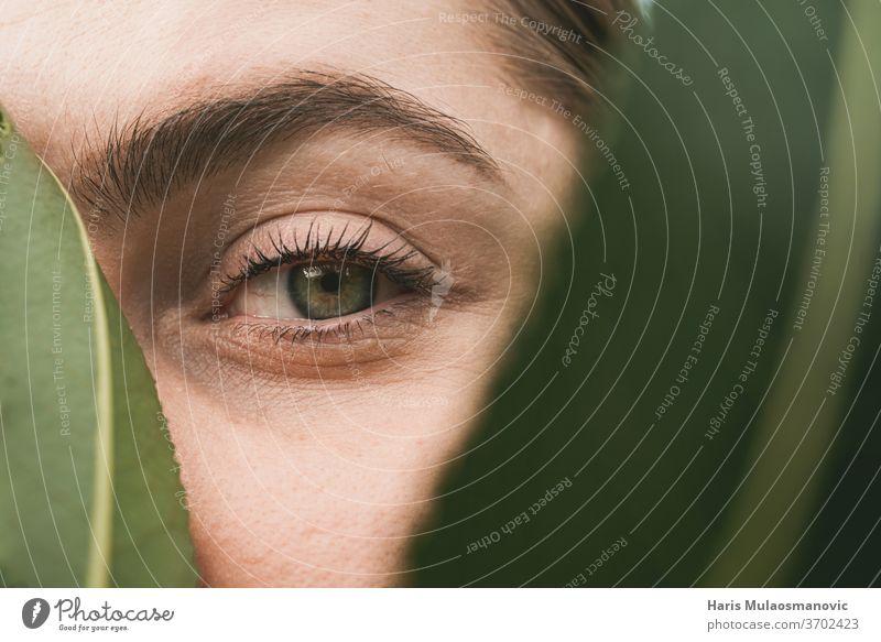 Frau Grüne Augen in Nahaufnahme mit Blatt bedeckt in der Natur Konzept von Schönheit und Natur attraktiv schön Kaukasier abschließen Korona Korona-Konzept