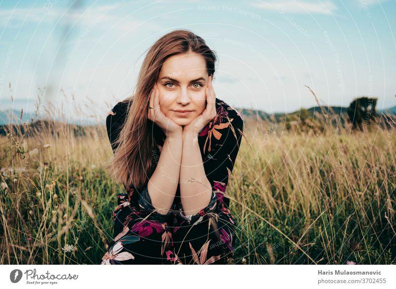 Blonde Frau im Blümchenkleid, die in die Kamera schaut und auf dem Grasfeld sitzt Erwachsener schön Schönheit blond blauer Himmel Kaukasier Kleid Gesicht Mode