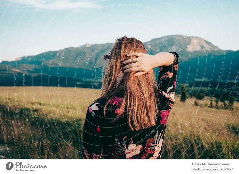 blonde Frau mit Blick auf die Berge der schönen Landschaft Erwachsener Schönheit blauer Himmel Kaukasier Kleid Gesicht Mode Feld Blumenkleid Freiheit Mädchen