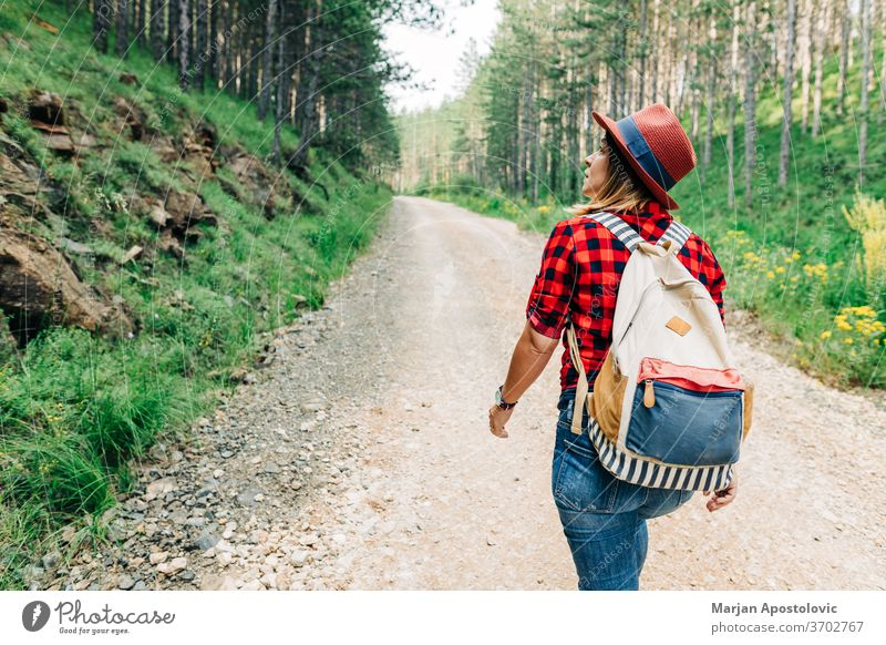 Junge Naturforscherin wandert auf unbefestigter Bergstraße aktiv Abenteuer allein Rucksack Schmutz Fundstück genießen erkunden Entdecker Frau Wald frei Freiheit