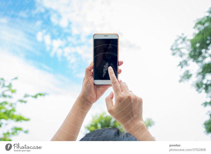 Frau hält Smartphone mit verschwommenem Himmelshintergrund in der Hand abstrakt Erwachsener Kunst Hintergrund blau Unschärfe Business Anruf Zelle Mitteilung
