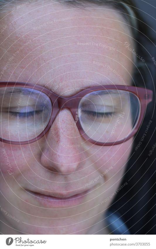 Gesicht einer lächelnden Frau mit Brille und geschlossenen Augen. Entspannung und Zufriedenheit brille entspannung zufriedenheit schlafen dösen