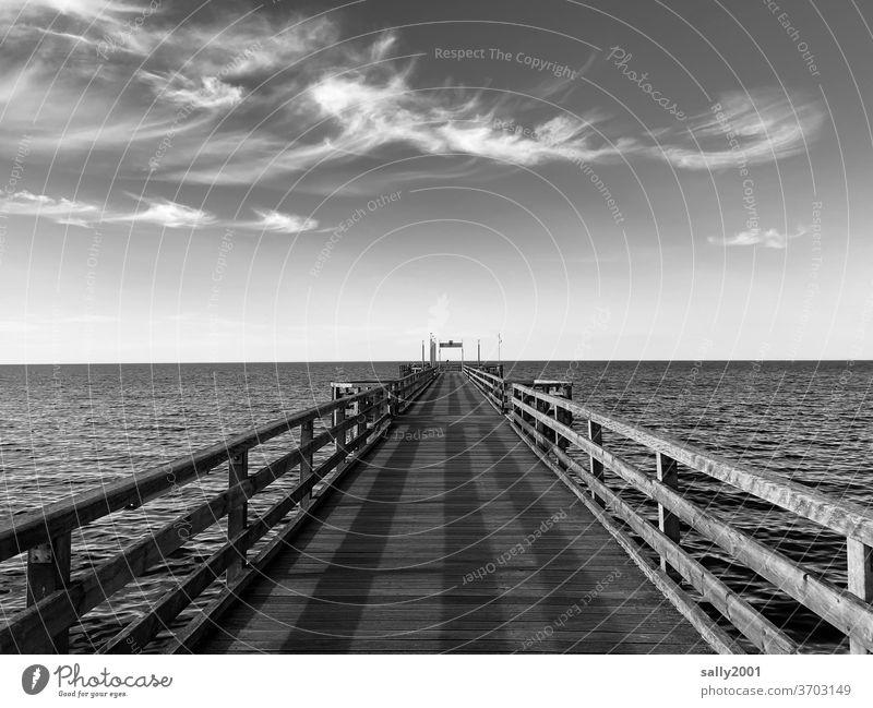 Brücke in die See... Seebrücke Heiligendamm Ostsee Steg Federwolken Meer Schwarzweißfoto Symmetrie Geländer Holzsteg Holzgeländer Hafen schönes Wetter