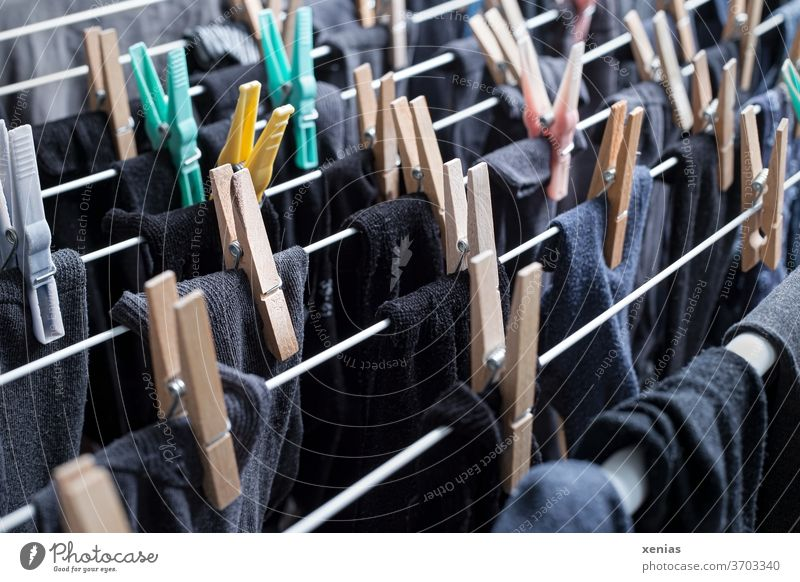 Dunkle Sockenwäsche - schwarze, graue und blaue Strümpfe hängen mit Wäscheklammern zum Trocknen auf dem Wäscheständer Klammer Haushalt Waschtag trocknen