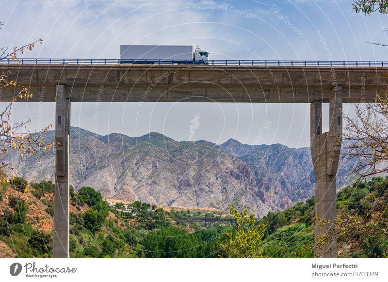 Lastwagen mit Kühlsattelanhänger überquert ein Viadukt mit einer Berglandschaft im Hintergrund Brücke Straße gekühlt Berge trayler Transport Verkehr Autobahn