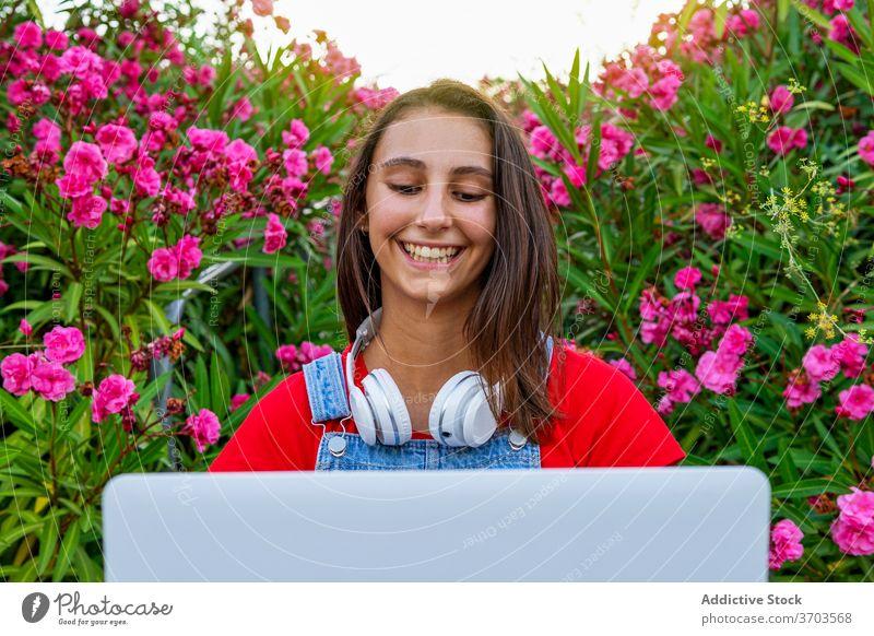 Fröhliche Frau mit Laptop in der Stadt Skateboard Skater benutzend Großstadt Lächeln Browsen tausendjährig Generation Wochenende Straße ruhen