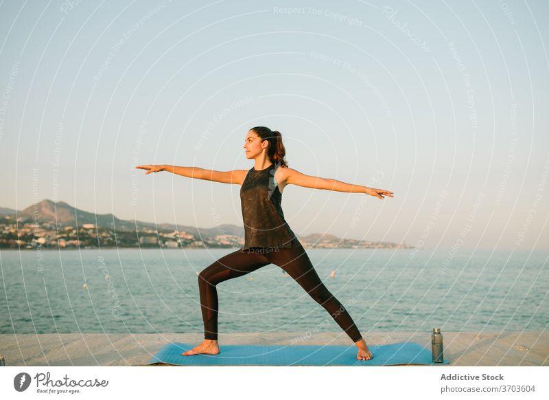 Ruhige Frau in Warrior Pose auf Yoga-Matte Krieger-Pose virabhadrasana Windstille üben MEER Barfuß Unterlage Sportbekleidung ruhig erstaunlich Meereslandschaft