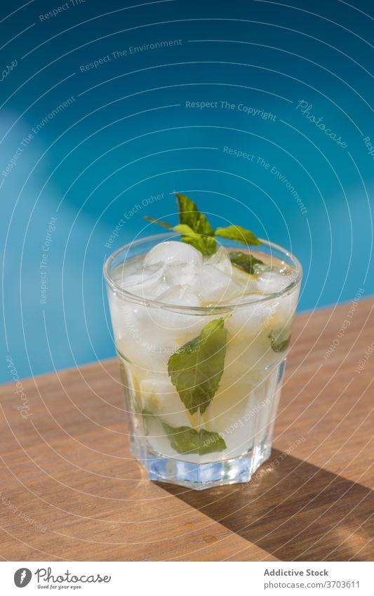 Glas Mojito-Cocktail am Schwimmbad trinken Pool Alkohol Eis Zitrone Minze kalt Getränk Zitrusfrüchte Erfrischung Frucht cool geschmackvoll lecker Feinschmecker