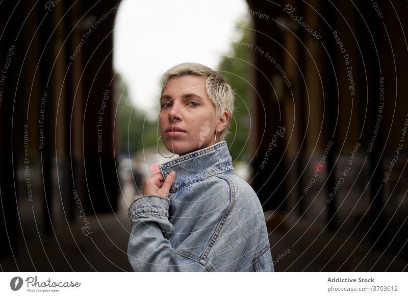Seriöse stilvolle Frau in der Stadt Model Jeansstoff Jacke Großstadt Straße Windstille ernst Stil trendy gewölbt Durchgang lässig besinnlich Outfit nachdenklich