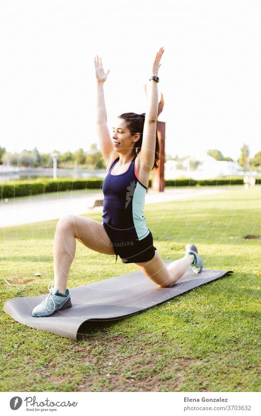 Junge brünette Frau im Park beim Trainieren und Dehnen auf einer Matte passen Yoga Fitness Übung Meditation Sport Gleichgewicht Pose Erholung Training