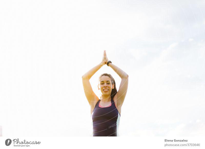 Fröhliche junge brünette Frau beim Training und Stretching im Park passen Yoga Fitness Übung Meditation Sport Gleichgewicht Pose Erholung trainiert.