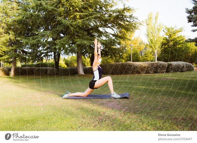 Junge brünette Frau mit Maske, die sich auf einer Matte im Park bewegt und streckt Mundschutz passen Yoga Pandemie COVID Fitness Übung Meditation Coronavirus
