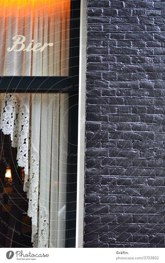 Meh' Bier unser Lebenselixir, Meh' Bier wozu sind wir sonst denn hier? Leicht schiefes Bild eines Kneipenfensters auf dem Bier angepriesen wird, doch ein Blick durch das Fenster verrät, dass die Kneipe geschlossen ist.