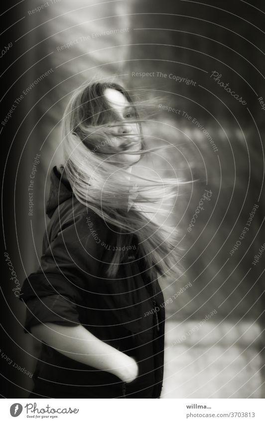 Mädchen mit langen Haaren im Wind junge Frau langhaarig Hände in den Taschen windig warten Jugendliche Mensch schön attraktiv stehen lässig sw Moment Innehalten