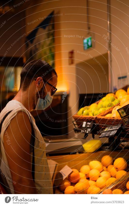 Mann mit Mundschutz/Maske beim Einkaufen im Supermarkt während der Corona Pandemie. Obst Maskenpflicht Geschäft Einzelhandel Alltag Lebensmittel