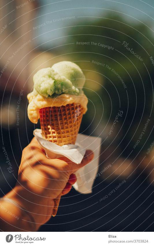 Eine Person hält eine Eistüte mit zwei Kugeln Eis in der Hand Eiskugeln Waffel Sommer lecker Eiswaffel Speiseeis Erfrischung Sonne gutes Wetter halten Eisdiele
