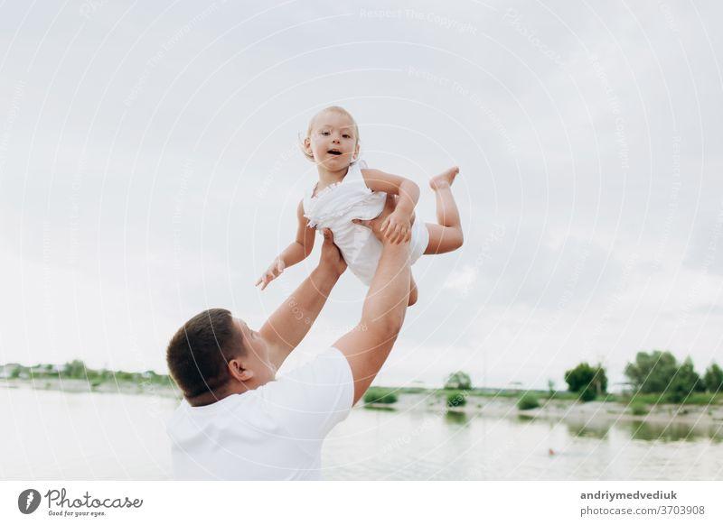 Vater wirft Baby auf Pier auf Seehintergrund, Mädchen fliegt in den Himmel. Portrait Vater mit Kind zusammen. Papa, kleine Tochter im Freien. Angelurlaub der Familie am Teich.