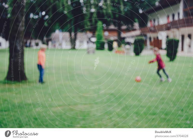 Zwei Kinder spielen Fußball auf Wiese, Foto ist unscharf Sport Ball Spielen Gras grün Rasen Ballsport Freizeit & Hobby Außenaufnahme Farbfoto Tag sportlich