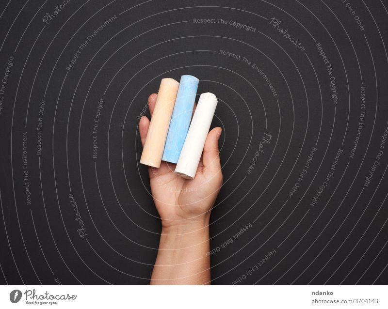 weibliche Hand hält dreifarbige Kreide auf dem Hintergrund einer leeren schwarzen Kreidetafel Kaukasier Tafel Kindheit Nahaufnahme hölzern Erwachsener blau