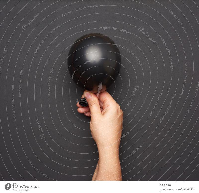 weibliche Hand, die einen aufgeblasenen schwarzen Luftballon auf schwarzem Hintergrund hält Air Spielzeug Überraschung gefüllt Frau nach oben Halt Bändchen