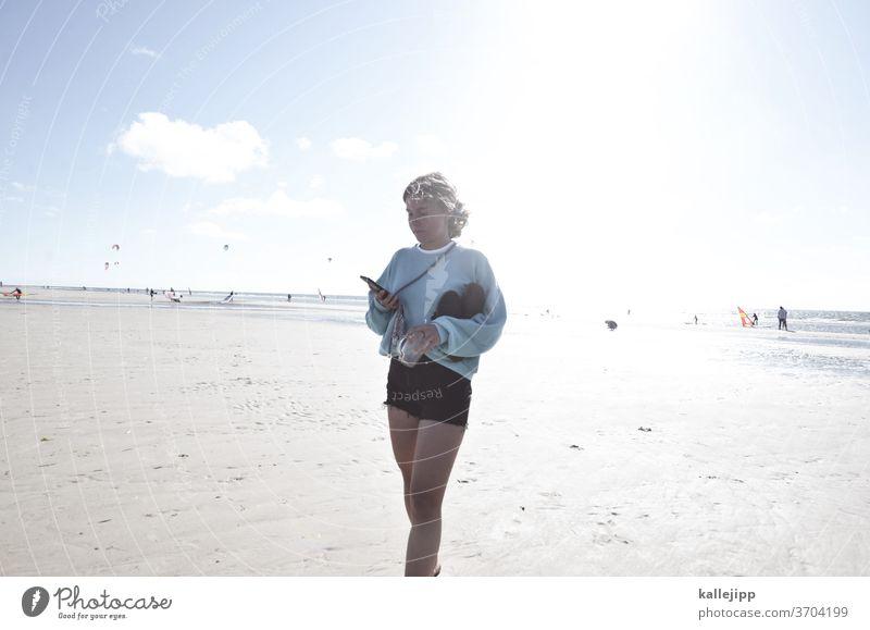 Mädchen am Strand mit Handy Teenagermädchen Teenagerin teenager Mobilität Sommer Shorts Außenaufnahme Frau Farbfoto Jugendliche Natur Junge Frau schön jung