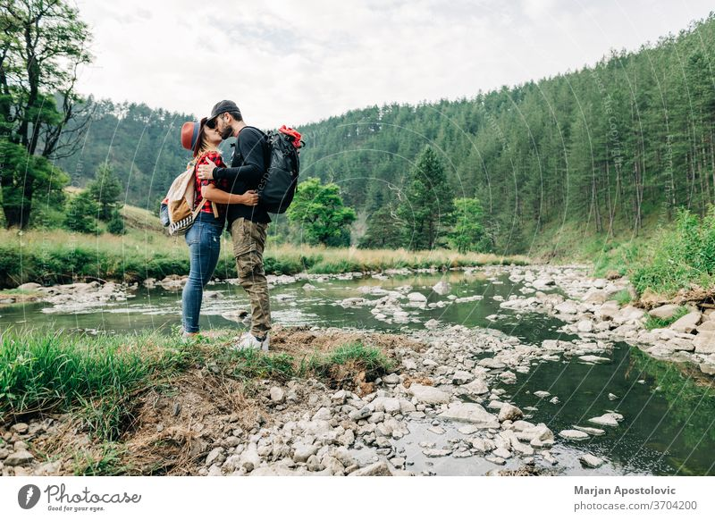 Junges Naturforscherpaar küsst sich in den Bergen am Fluss Erwachsener Abenteuer Rucksack Backpacker lässig Paar Bach Expedition Erkundung erkunden Wald Glück
