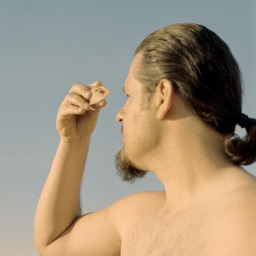 Spiegelung des Auges in einem zerbrochenen Stück Spiegel. Männliches Porträt, inneres Selbst und psychologisches Konzept. Gedreht auf analogem Film. Menschen