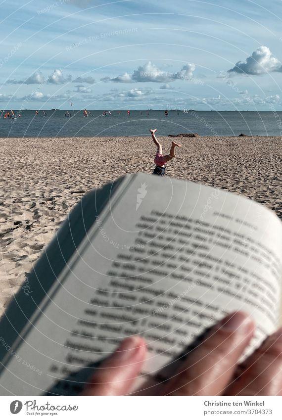 Gegensätze | Ruhe und Bewegung am Strand... Urlaub Strandleben Lesen Kind Turnen Nordseestrand Erholung Buch Sand Sommerhimmel himmelblau Rad schlagen Hände