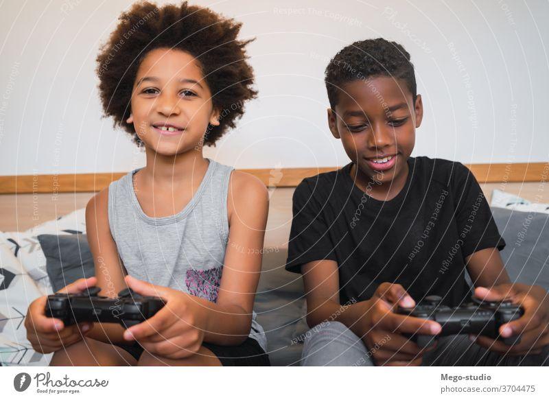 Zwei Brüder spielen zu Hause Videospiele. Zusammensein Spiel Regler Afroamerikaner Aussehen im Innenbereich Kinder Entertainment Aktivität heiter Spaß Porträt