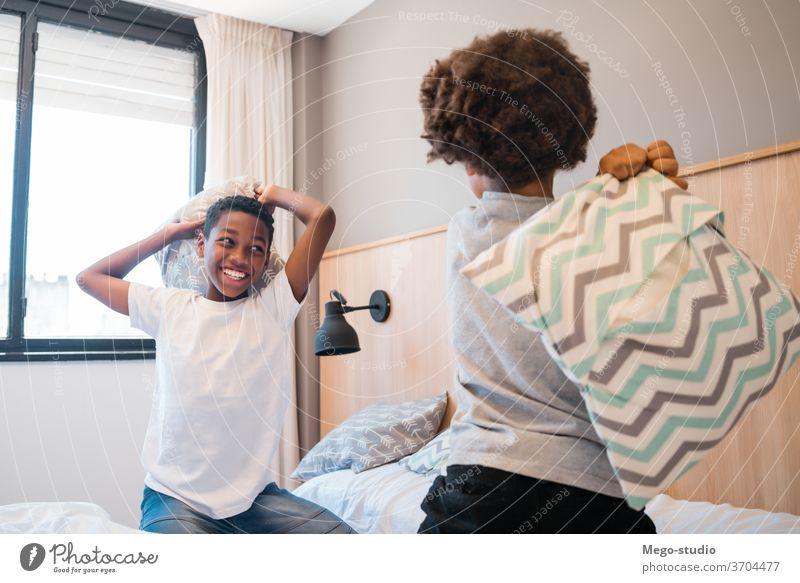 Zwei Brüder spielen zu Hause mit Kissen. Kinder Zusammensein Bruder Glück Schlafzimmer aufgeregt Porträt positiv aktiv Kissenschlacht bezaubernd Lifestyle