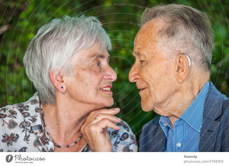 Ehepaar im Ruhestand kurz vor einem Kuss Zärtlichkeit Person Glück verheiratet 80 Jahre alt Partnerschaft Park Intimität charmant Nähe nebeneinander