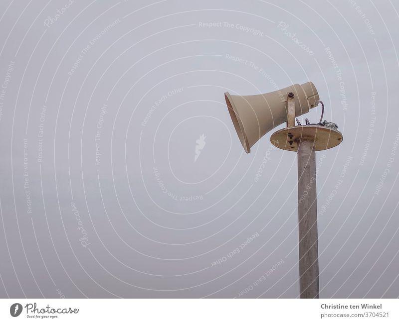 Seitenansicht eines älteren Lautsprechers in Form eines Megaphons vor diesigem Himmel Megafon Mast Kommunizieren Durchsage Information Hintergrund neutral grau