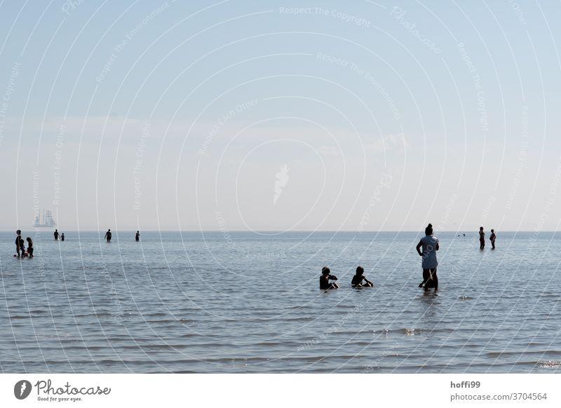 die Menschen erfrischen sich in der auflaufenden Flut -Sommerfrische am Meer sommerfrische Wattenmeer baden seichtes Wasser auflaufendes Wasser Nordsee Horizont