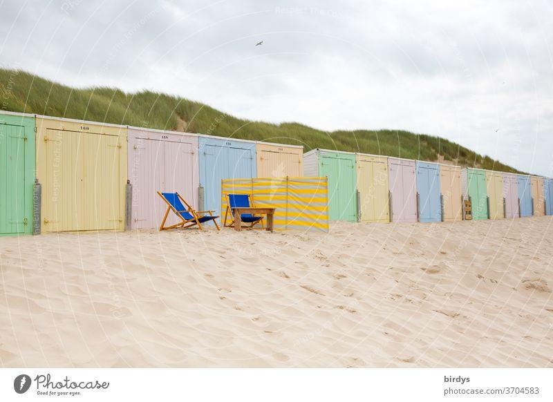 pastellfarbene Strandhütten in einer langen Reihe. 2 leere Liegestühle und ein Windschutz davor Sand Pastellton bunt mehrfarbig Nordseestrand Dünen