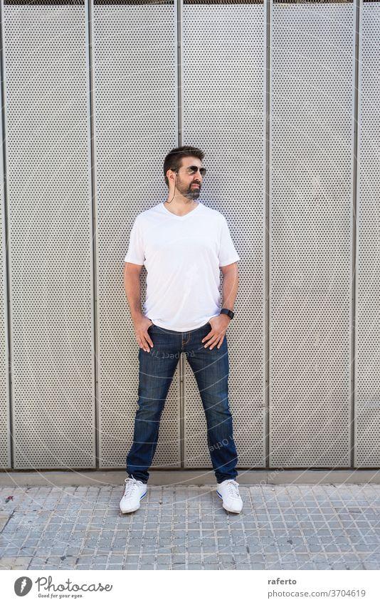 Bärtiger Mann mit Sonnenbrille, der mit den Händen auf der Tasche an einer Metallwand lehnt und dabei wegschaut 1 Wegsehen Handtasche Wand bärtig Stehen