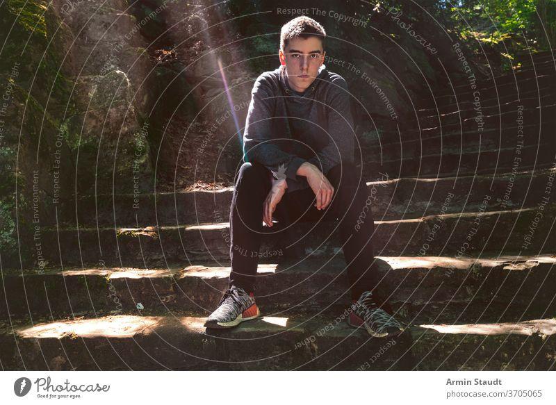 Porträt eines ernsthaften jungen Mannes, der auf einer Treppe sitzt Sitzen bw cool lässig Sonnenlicht Sonnenstrahlen im Freien Perspektive trendy selbstbewusst