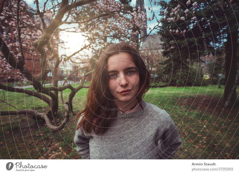 Porträt einer jungen, lächelnden Frau in einem Park vor einem Magnolienbaum im Freien Lächeln schön Natur Kirche Frühling Blüte glücklich froh Aussehen