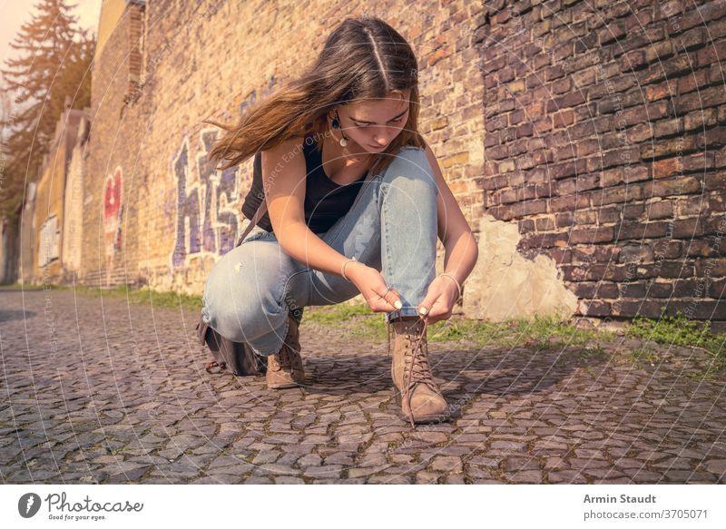 junge Frau in Sommerkleidung bindet ihre Schuhe hockend Straße im Freien schön konzentriert Tasche Wand Baustein Berlin Lifestyle Straßenbelag Teenager Mädchen