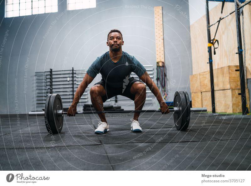 Crossfit-Sportler, der mit einer Langhantel trainiert. Mann Fitness Curl-Hantel Training Übung Muskeln Konzentration Crossfit-Training sportlich Konzept