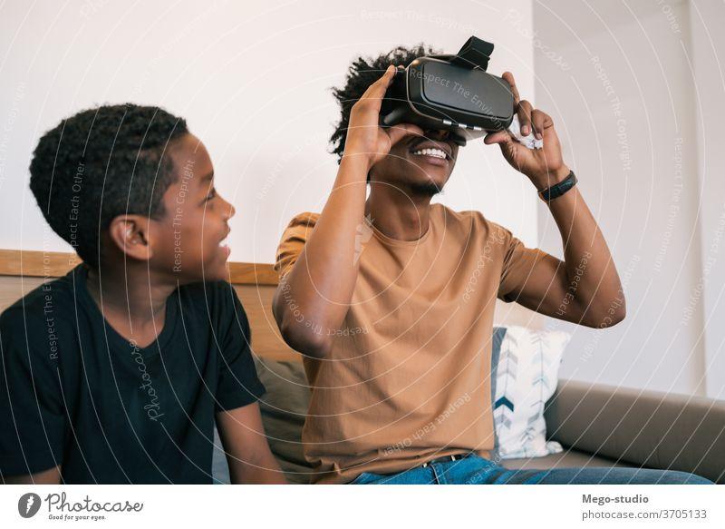 Vater und Sohn spielen mit VR-Brillen. Spiel Video Zusammensein Afroamerikaner entspannend bezaubernd elektronisch Partnerschaft Videospiel