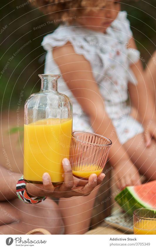 Anonyme Person mit Natursaft beim Picknick Saft orange trinken natürlich Sommer Frucht frisch Vitamin Lifestyle Wochenende Familie dienen Saison lecker