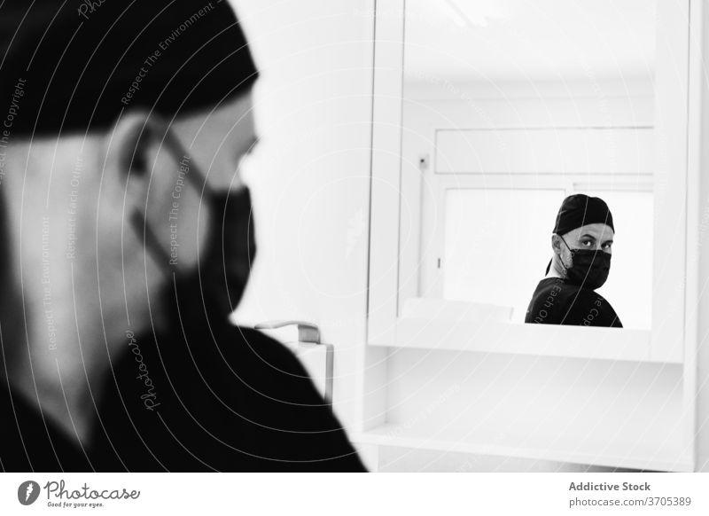 Männlicher Tätowierer in Maske im Salon Tattoo Meister Mann Mundschutz vorbereiten Arbeit angezogen Spiegel männlich professionell Konzentration behüten ernst