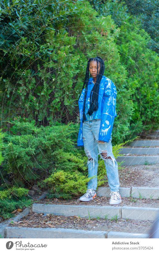Modische schwarze Frau steht auf Stufen im Park Mode Stil Afroamerikaner trendy jung Hipster Geflecht urban Streetstyle ethnisch tausendjährig Jeanshose Jacke