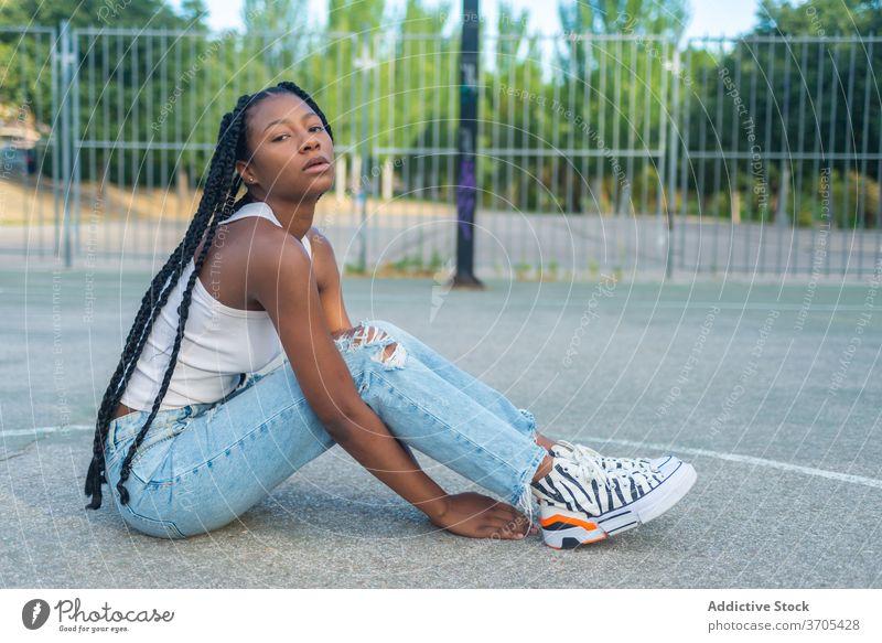 Junge schwarze Frau sitzt auf Sportplatz urban Stil Streetstyle trendy Hipster jung Sportpark Geflecht ethnisch tausendjährig Jeanshose Basketball Outfit Mode