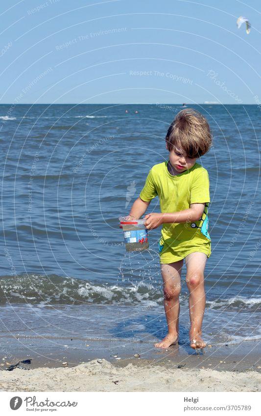 Wasserträger am Nordseestrand Junge Mensch Kind Strand Meer spielen Eimer tragen transportieren Sand Horizont Natur Umwelt Freude Spaß Spielen