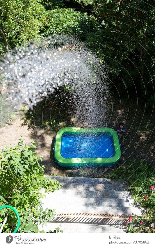Ein Planschbecken im Garten das vom Balkon aus befüllt wird.  Wasserstrahl Sommer Hitze Abkühlung Wassertropfen Erfrischung Sonnenlicht Freude Vogelperspektive